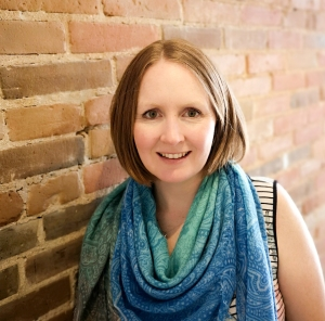 Image of Kim Callaghan, content writer, with brick wall background.